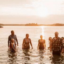 En liten grupp människor som står i vattnet under en solnedgång.