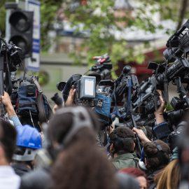 På bilden trängs journalister som håller kameror och mikrofoner över sina huvuden.