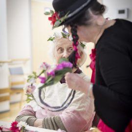 På bilden tittar en äldre dam på då en person utklädd till clown binder en blomsterkrans.