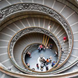 En spiraltrappa med utsmyckade ledstänger är fotograferad ur fågelperspektiv.